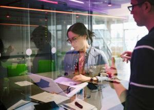 Junge Frau mit schwarzen Haaren arbeitet an einem Laptop