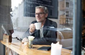 Mann mit grauen Haaren sitzt in einem Café und trinkt Kaffee