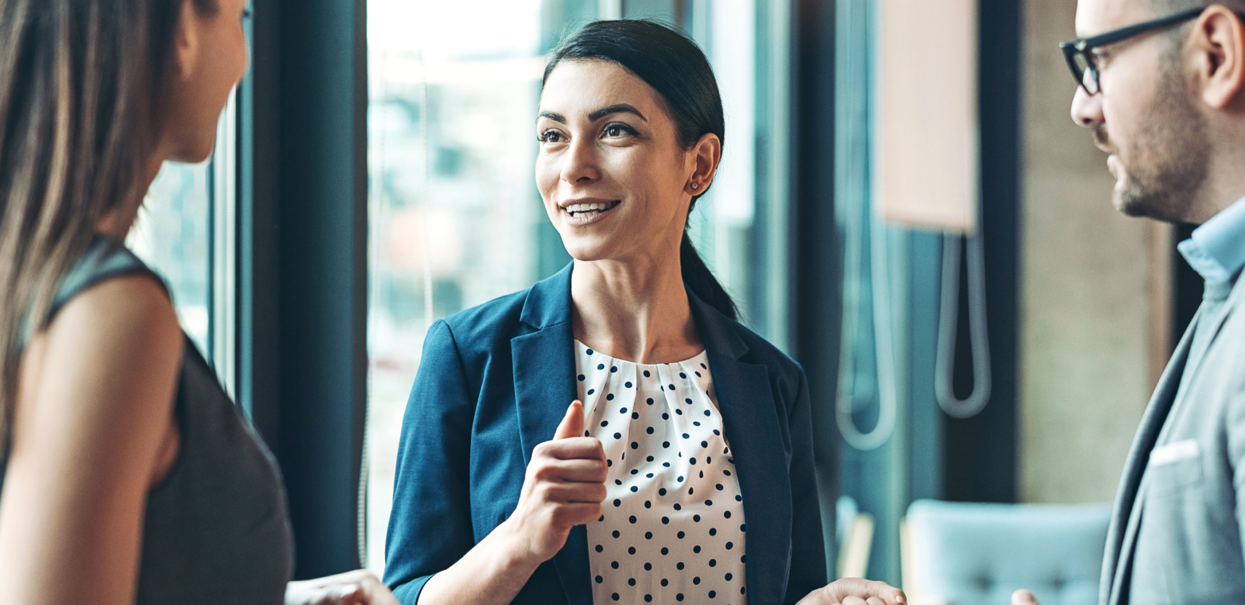 Lächelnde Frau im Gespräch mit Kollegen