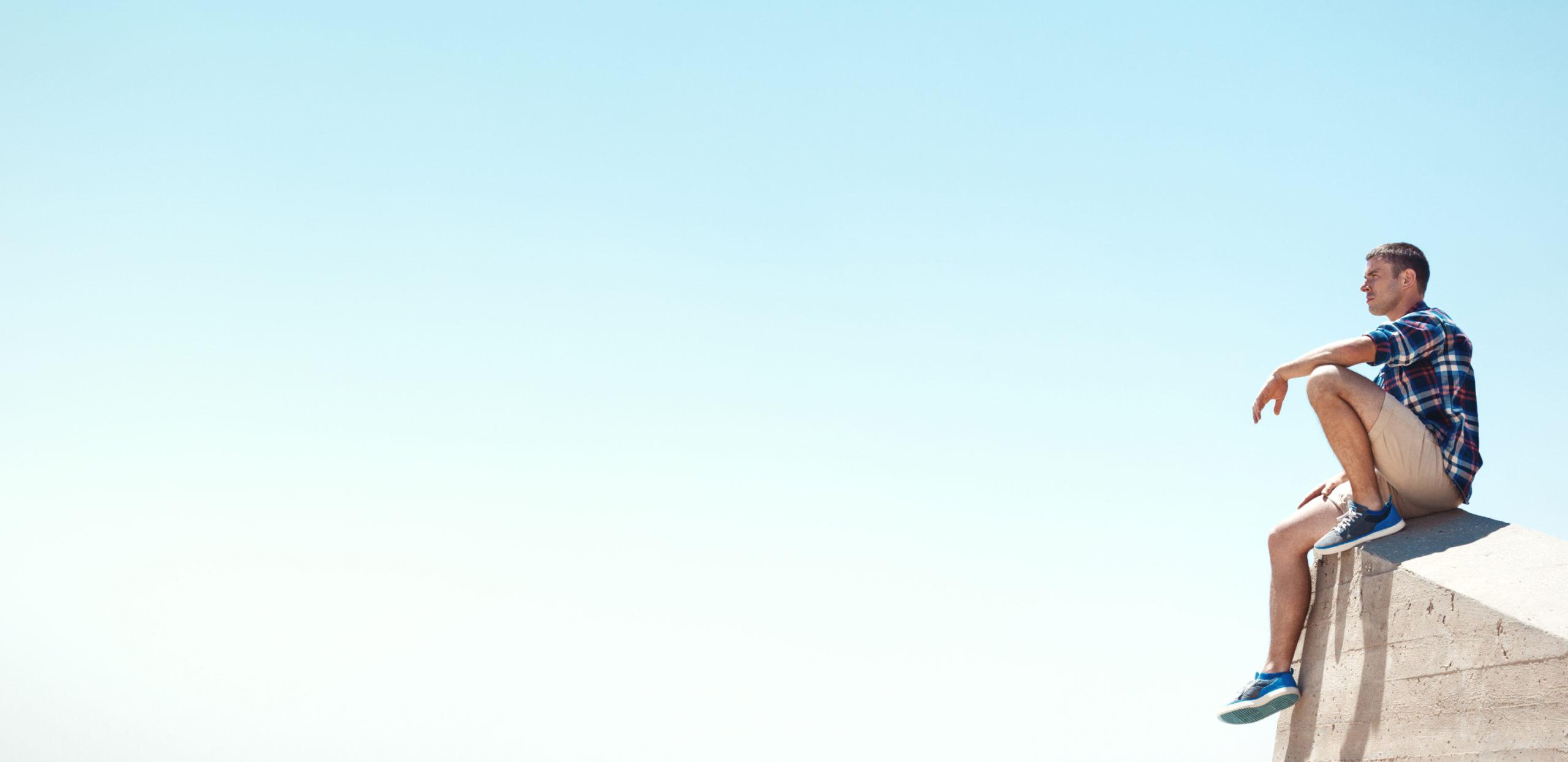 Mann mit kurzen Hosen genießt das sonnige Wetter