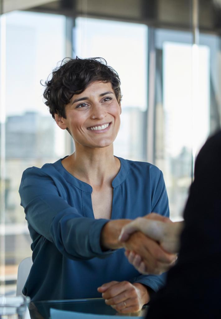 Frau mit kurzen schwarzen Haaren schüttelt einer weiteren Person die Hand