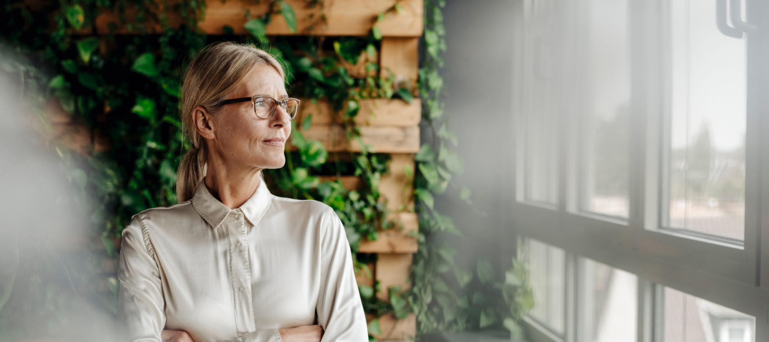 Frau schaut vor begrünter Wand aus dem Fenster
